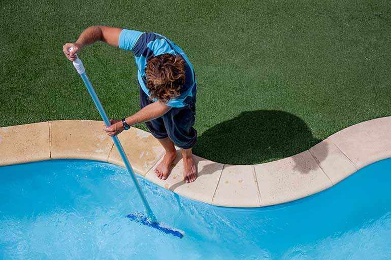 man cleaning inground pool